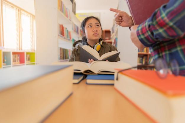 Dans la bibliothèque - un enseignant enseigne à l'étudiant en bibliothèque