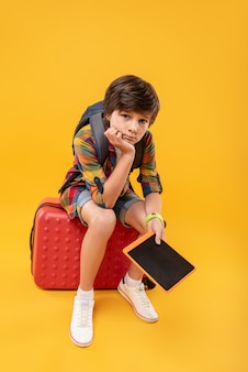 Dans le bleu. adorable garçon ennuyé tenant sa tablette alors qu'il était assis sur ses bagages
