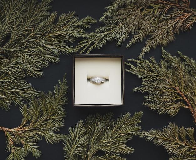 Dans la boîte à bijoux, il y a une bague avec un cadre en branches de genévrier sur un beau fond noir. notion romantique. style plat.