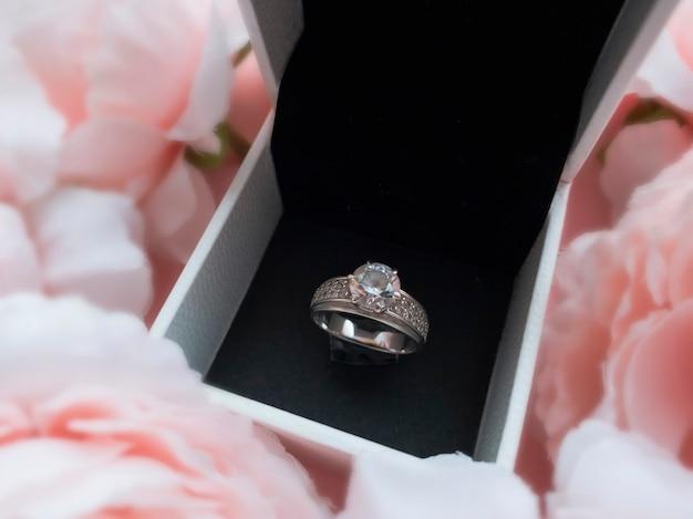 Dans la boîte à bijoux, il y a une bague dans un cadre de pivoines roses délicates sur un beau fond rose. notion romantique. style plat.
