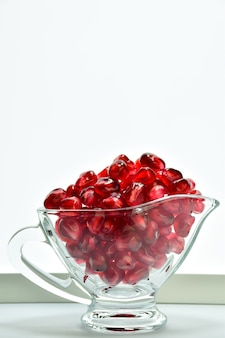 Dans un bol en verre transparent avec une poignée, des grains de grenade rouge vif juteux sont versés