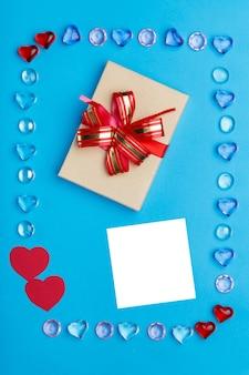 Dans un cadre fait de galets de coeurs sur une surface bleue, une boîte avec un arc