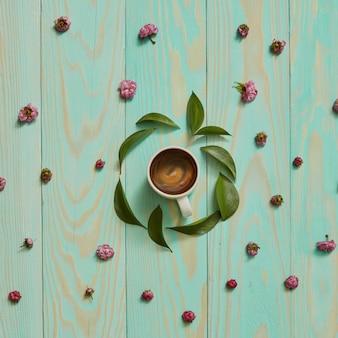 Dans un cadre rond avec des feuilles et des fleurs roses, une tasse de café noir à plat