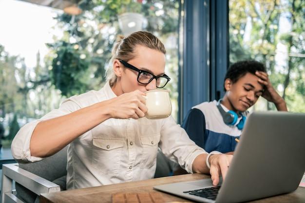 Dans le café. bel homme agréable ayant une boisson savoureuse tout en travaillant sur l'ordinateur portable dans le café