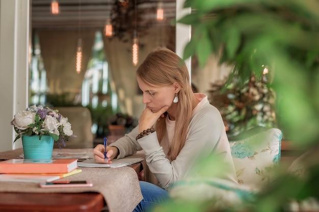 Dans un café, une fille s'assoit à une table et feuillette un livre.