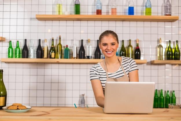 Dans le café. ravi joyeux belle femme souriante et vous regarde tout en utilisant un ordinateur portable pour le travail