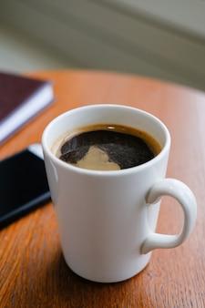 Dans le café sur une table en bois, il y a une tasse blanche avec un cappuccino