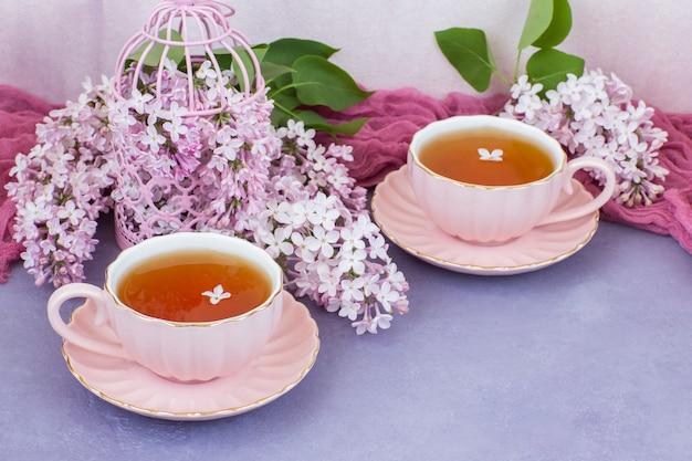 Dans une cage rose lilas rose et deux tasses de thé