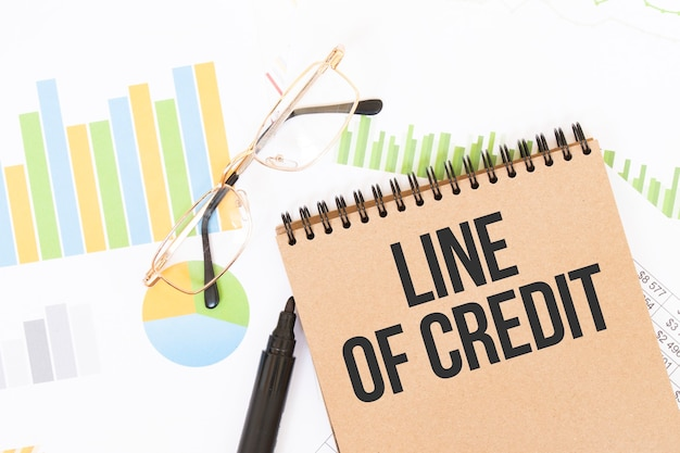 Dans un cahier de couleurs artisanales se trouve une inscription ligne de crédit, à côté de crayons, de lunettes, de graphiques et de diagrammes.