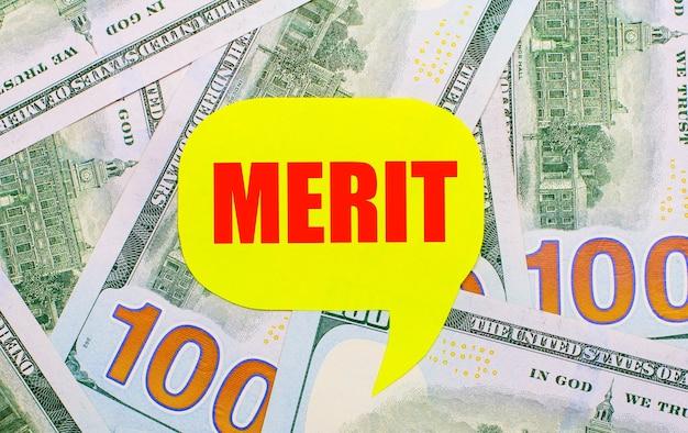 Dans le contexte des dollars éparpillés sur la table se trouve une carte jaune bouclée avec le texte merit. notion financière