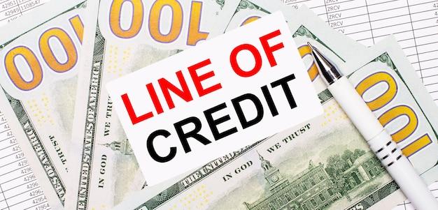 Dans le contexte des rapports et des dollars - un stylo blanc et une carte avec le texte ligne de crédit