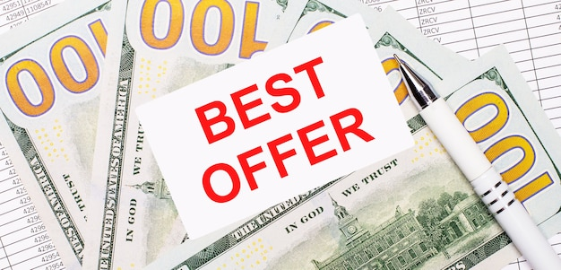 Dans le contexte des rapports et des dollars - un stylo blanc et une carte avec le texte meilleure offre. concept d'entreprise