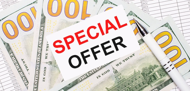 Dans le contexte des rapports et des dollars - un stylo blanc et une carte avec le texte offre spéciale. concept d'entreprise