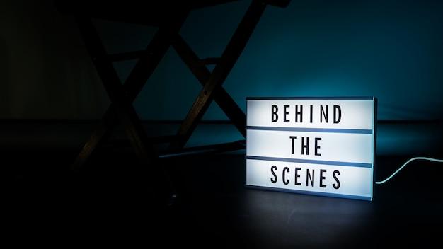 Dans les coulisses de la boîte à lumière. texte sur la boîte à lumière du cinéma. mégaphone et chaise de réalisateur et ardoise de cinéma à côté. derrière le concept de scène.