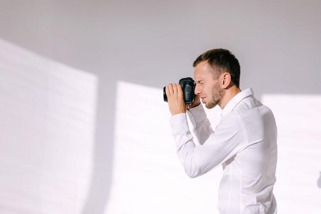 Dans les coulisses du photographe travaillant en studio blanc prenant des photos