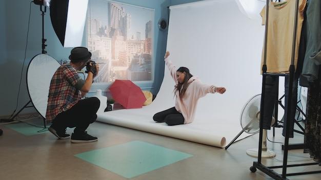 Dans les coulisses de la séance photo: mannequin noir assis par terre et posant pour un photographe