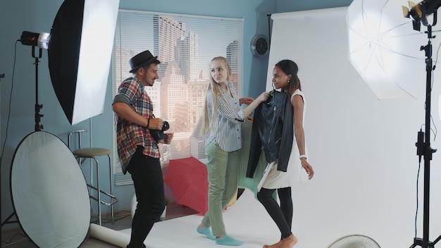 Dans les coulisses de la séance photo: un photographe avec une assistante choisit des vêtements pour la séance photo du mannequin