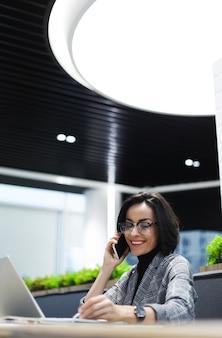 Dans le coworking. photo vue latérale d'une femme joyeuse vêtue de vêtements décontractés et élégants, parlant au téléphone tout en travaillant sur son ordinateur portable.