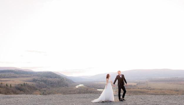 Dans le crépuscule avec un beau paysage, un couple de mariés se tient la main et se regarde