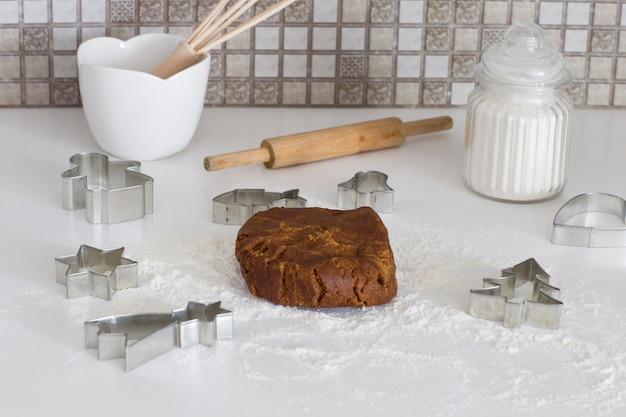 Dans la cuisine, sur la table, des moules à pâtisserie, de la pâte à biscuits au gingembre, de la farine et un rouleau à pâtisserie