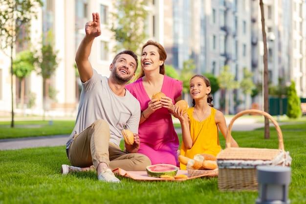 Dans cette direction. joyeux homme positif pointant avec sa main tout en montrant quelque chose d'intéressant à sa famille