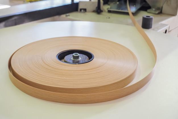 Dans une fabrique de meubles, un rouleau en plastique de bord est introduit dans une machine de bande de chant.