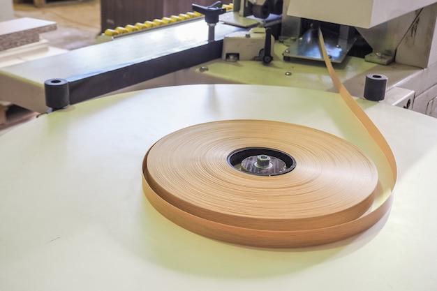 Dans une fabrique de meubles, un rouleau en plastique de bord est introduit dans une machine à plaquer les bords.