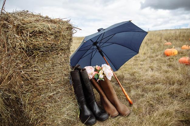 Dans la ferme. composition de bottes en caoutchouc, parapluie, paille et fleurs.