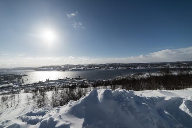 Dans le grand nord froid un étang, le soleil du matin brille et beaucoup de neige