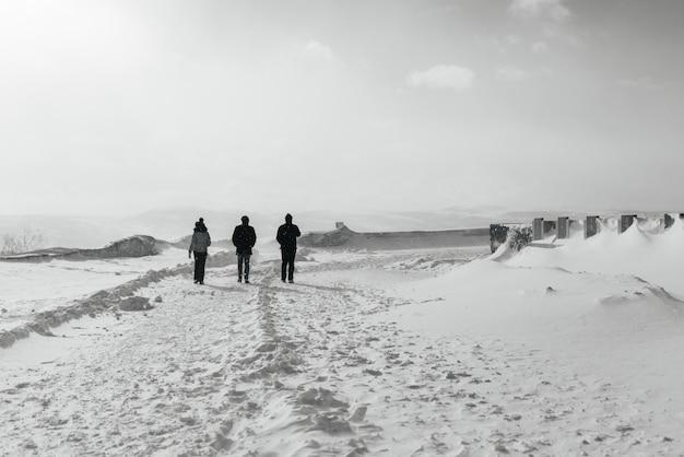Dans le grand nord froid, trois personnes marchent le long du champ enneigé
