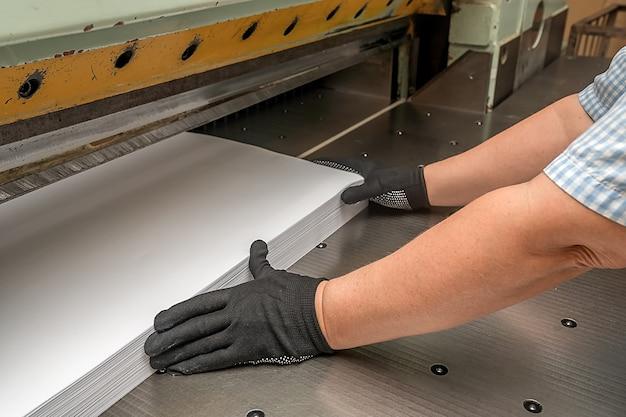 Dans l'industrie de l'imprimerie, des mains tiennent le papier sous une guillotine. un couteau tranchant coupe le papier.