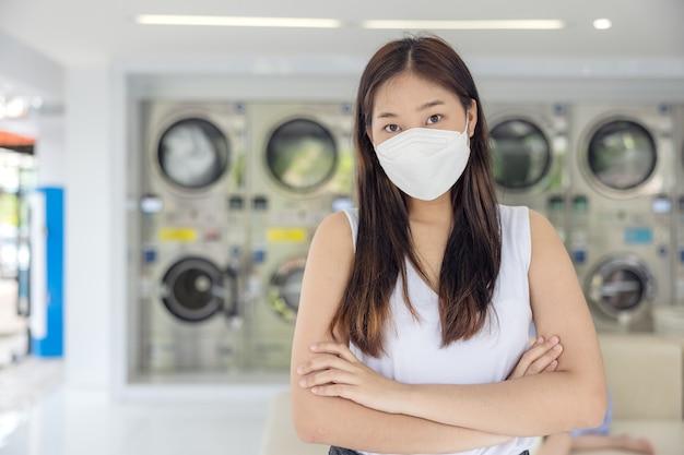 Dans la laverie en libre-service avec des machines à sécher en toile de fond, une jeune femme savoure des vêtements propres et repassés.