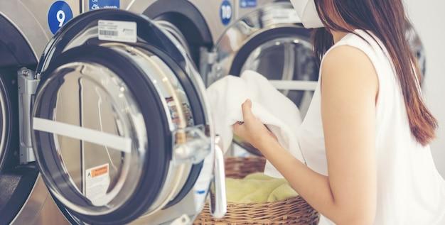 Dans la laverie libre-service avec sèche-linge en toile de fond, une jeune femme profite d'un repassage propre