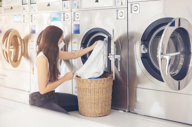 Dans une laverie avec de nombreuses machines à laver automatiques, une belle femme portant un masque fait la lessive.