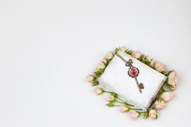 Dans le livre blanc sont des roses roses et une vieille clé avec un coeur