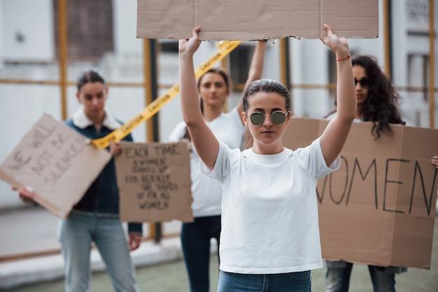 Dans les lunettes. un groupe de femmes féministes protestent pour leurs droits en plein air