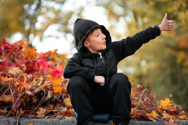 Dans un magnifique parc d'automne, un garçon est assis à la frontière, qui montre un pouce levé.