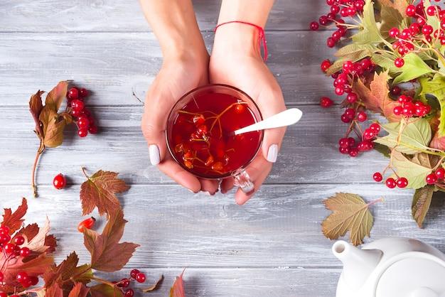 Dans une main féminine, une tasse de thé de vitamine berry sur un fond en bois gris avec espace de copie.