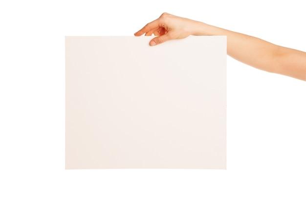 Dans la main une grande feuille de papier blanc montrée vers le bas. isolé, sur fond blanc.