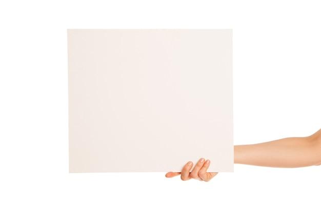 Dans la main une grande feuille de papier blanc s'affiche. isolé, sur fond blanc.