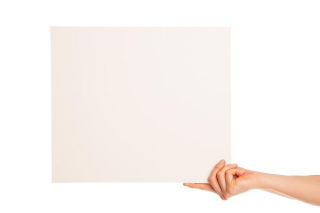 Dans la main une grande feuille de papier blanc s'affiche. la main tient le bord. isolé, sur fond blanc.