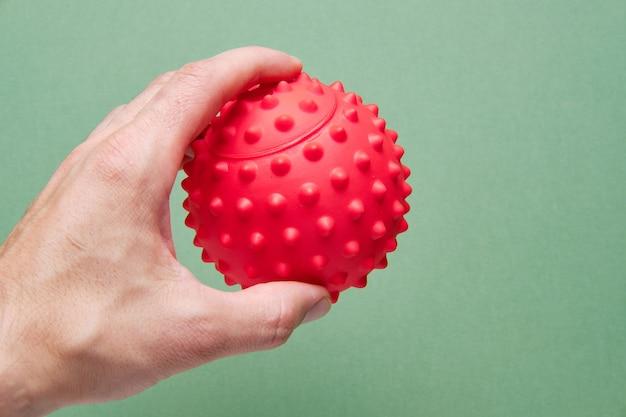 Dans la main d'un homme, une balle pour travailler les points de déclenchement ou une balle de physiothérapie pour la réflexologie