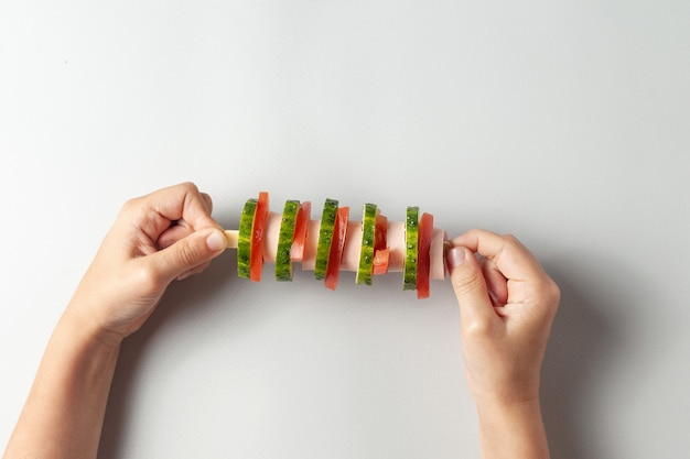 Dans Les Mains D'un Enfant Un Sandwich Inhabituel Sur Une épée. Il Y A Une Saucisse, Un Concombre, Une Tomate Photo Premium