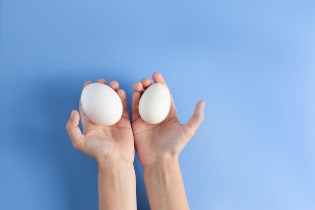 Dans les mains des enfants, deux œufs blancs. sur un fond bleu, les mains se trouvent. vue de dessus