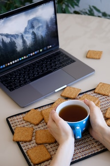 Dans les mains des femmes, une tasse de thé ou de café. à côté de l'ordinateur portable.