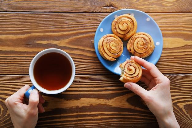 Dans les mains de la fille et une tasse de biscuit au thé noir mordu. à côté des petits pains à la cannelle faits maison sur une assiette bleue sur une table en bois