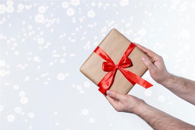 Dans les mains d'un homme boîte avec un cadeau