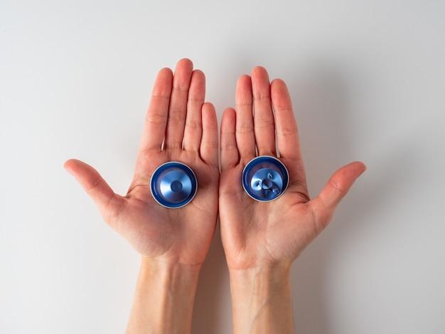 Dans les mains des hommes se trouvent deux capsules de café en aluminium bleu l'une des capsules est utilisée