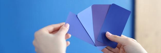 Dans les mains de la palette avec des nuances bleues contre un mur bleu sélection de peinture pour murs et façades