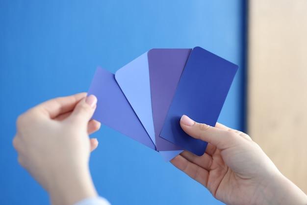Dans les mains de la palette avec des nuances bleues contre le mur bleu
